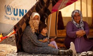 Grandmother and mother with disabled child, exhausted from the long way from Syria to Iraq