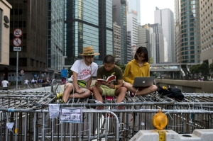 Protesters sit on road block setup by activists, as they block the main street to the financial Central district in Hong Kong
